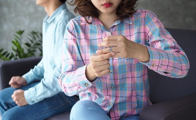 Mulher asiática está removendo o anel de casamento atrás do marido