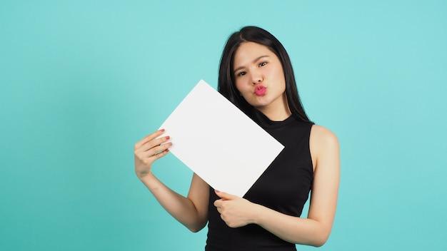 Mulher asiática está segurando a placa de papel vazio em branco sobre fundo verde ou menta ou azul tiffany.
