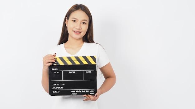 Mulher asiática está segurando claquete preta ou claquete de filme e usa aparelho no fundo branco