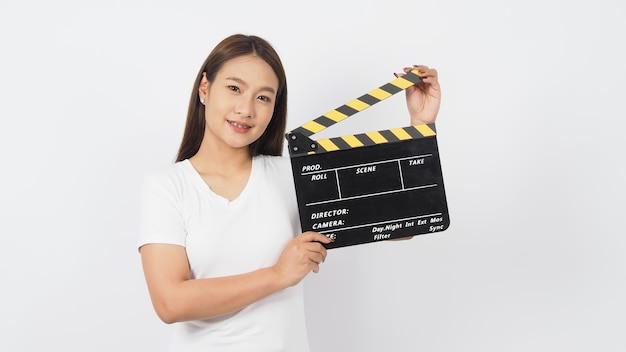Mulher asiática está segurando claquete preto ou ardósia de filme ou claquete e usar o aparelho no fundo branco.