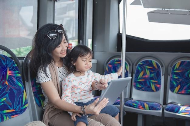 Mulher asiática está segurando sua filha e mostrando tablet