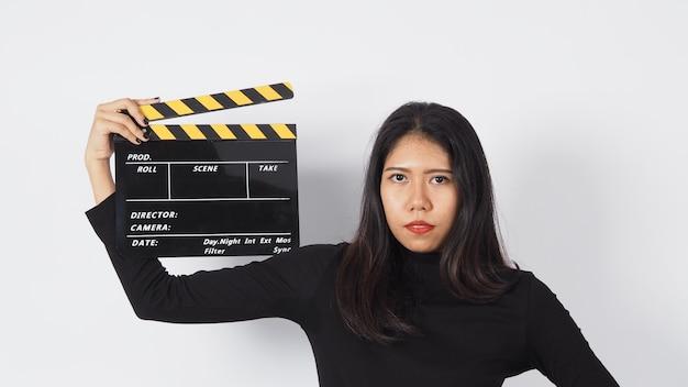 Mulher asiática está segurando um claquete preto ou uma tela de cinema ou uma ripa para uso na produção de vídeo