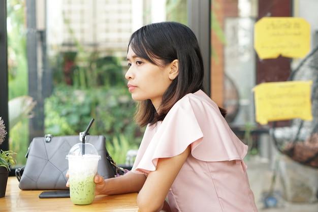 Mulher asiática está sentado bebendo chá verde em uma cafeteria.
