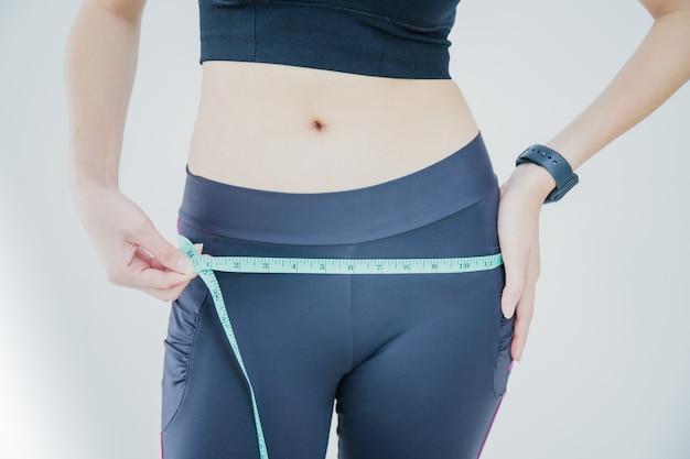 Mulher asiática está usando a fita métrica para medir em torno do quadril e em pé após o exercício.