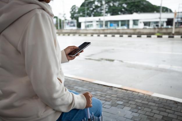 Mulher asiática está usando um smartphone, verificando a rede de mídia social enquanto espera o táxi no ponto de ônibus em dia chuvoso.