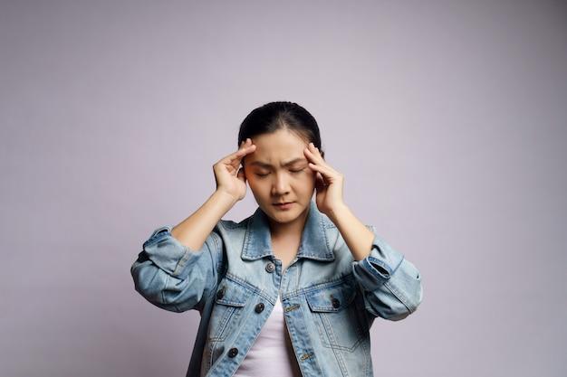 Mulher asiática estava doente com dor de cabeça tocando sua cabeça isolada.