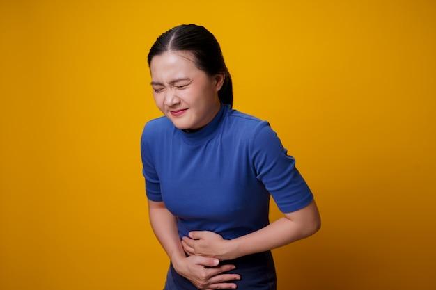 Mulher asiática estava doente com dor de estômago, segurando as mãos pressionando seu abdômen.