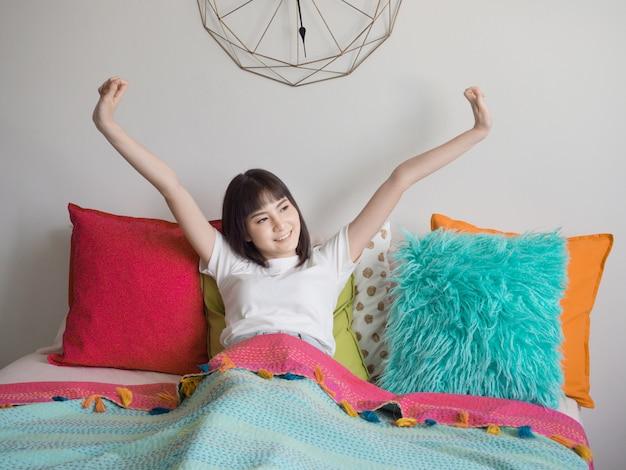 Mulher asiática, estendendo-se na cama depois de acordar