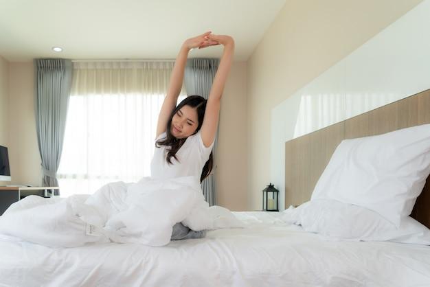 Mulher asiática, esticando as mãos e o corpo na cama