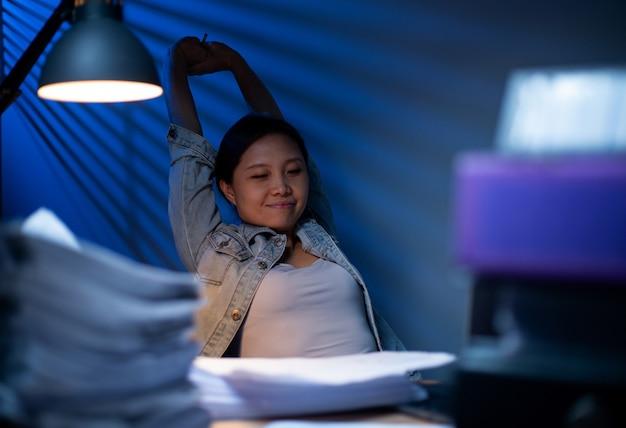 Mulher asiática esticando os músculos para relaxar depois de terminar seu trabalho no escritório. horas extras sozinhas, trabalhando para limpar seu projeto de documento. momento feliz e vida de liberdade de mente fresca remota.