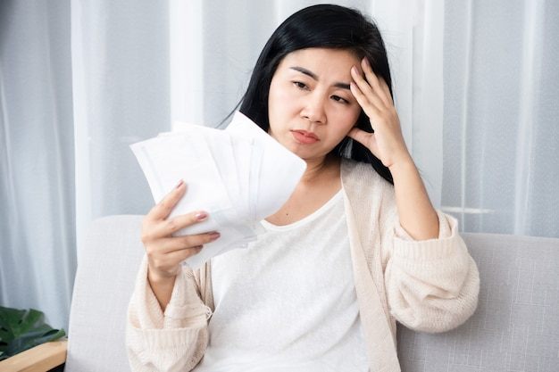 Mulher asiática estressada segurando muitas notas e tendo um problema de falência de dívidas