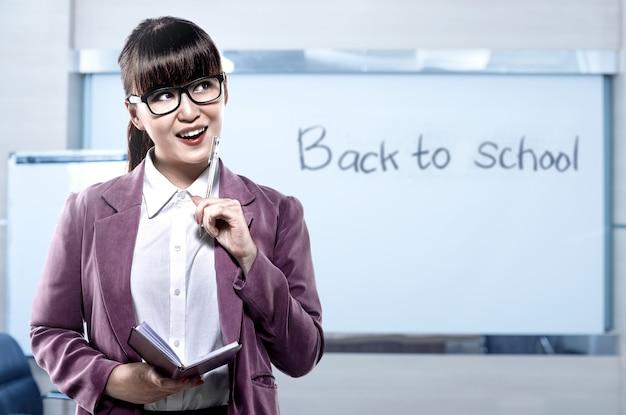 Mulher asiática estudante com caderno e caneta pensando em algo na sala de aula