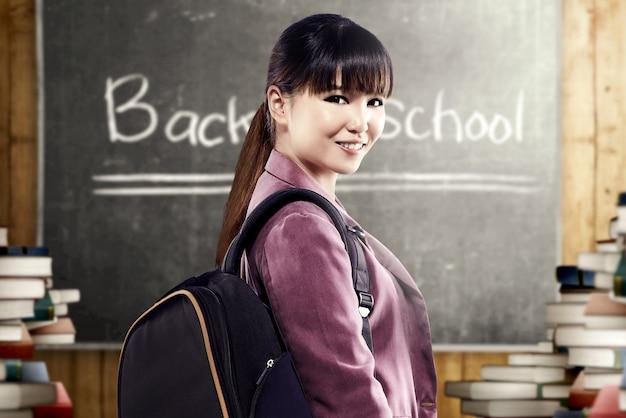 Mulher asiática estudante com mochila de pé e olhar para trás na sala de aula