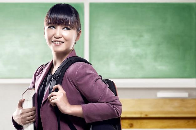 Mulher asiática estudante com mochila escriturada em pé e olhar para trás na sala de aula com lousa