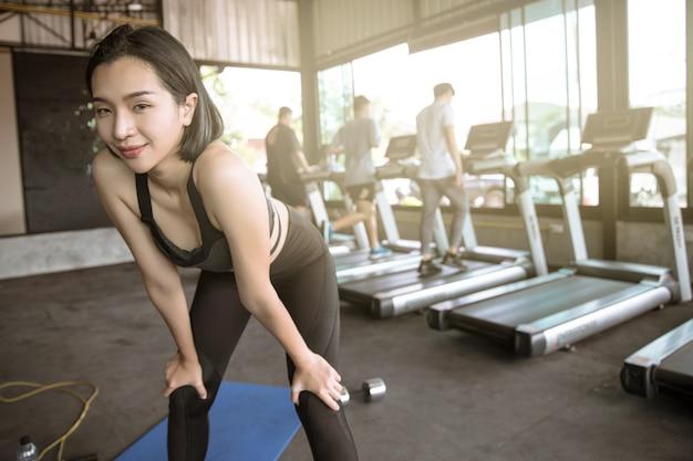 Mulher asiática exercícios no ginásio. fundo é pessoas correndo.