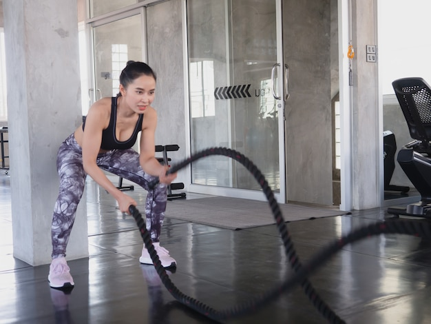 Mulher asiática, exercitando com cordas de batalha no ginásio
