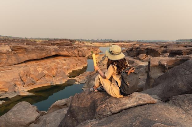 Mulher asiática exploradora sentada em um penhasco rochoso olhando um mapa de papel no grande cânion sam phan bok da tailândia