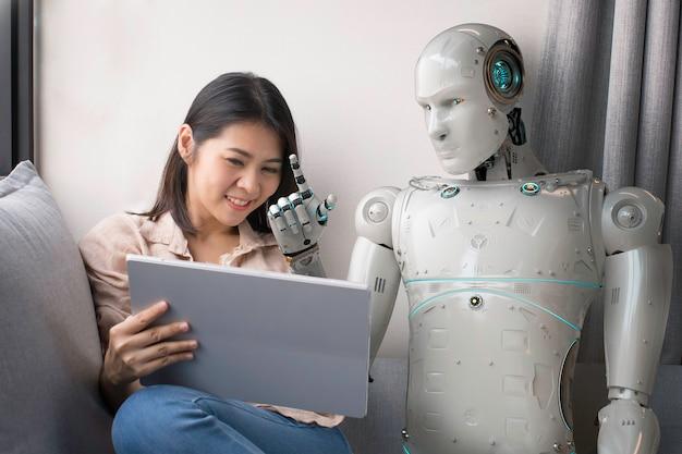 Mulher asiática falando com o robô enquanto usa o tablet digital em casa