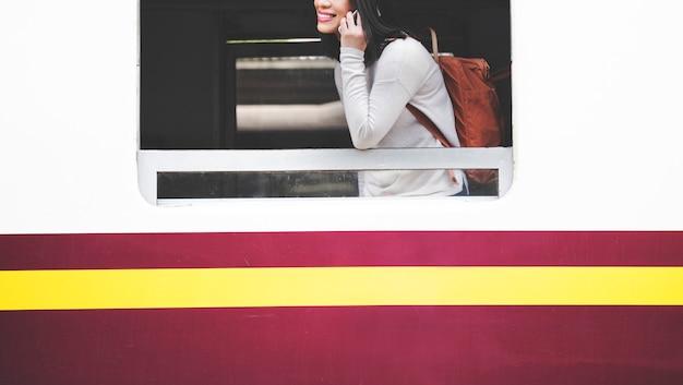 Mulher asiática, falando no celular no trem