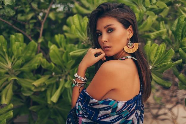 Mulher asiática fascinante com pele bronzeada posando sobre palmeiras verdes