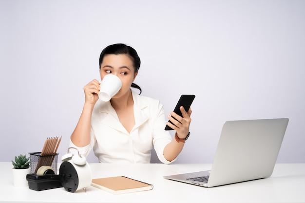 Mulher asiática faz uma pausa depois de trabalhar e usar o telefone inteligente. isolado no fundo branco.