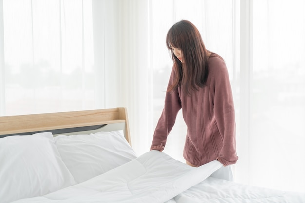 Mulher asiática fazendo cama em quarto com lençol branco limpo