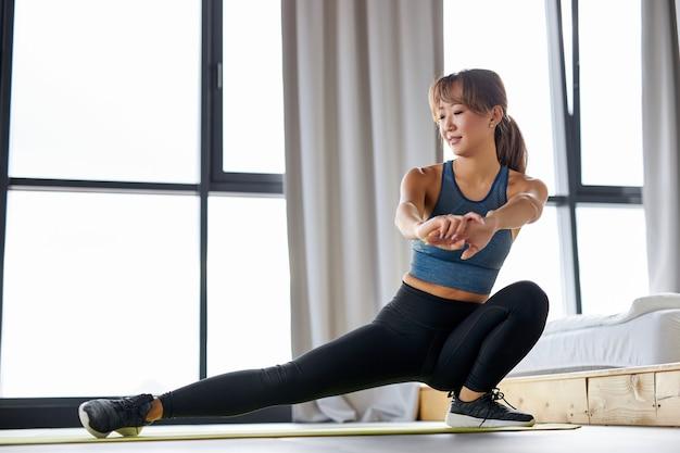 Mulher asiática fazendo estocadas em um tapete de ioga em uma sala iluminada, uma senhora atraente em roupas esportivas faz exercícios de treino