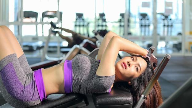 Mulher asiática fazendo exercícios de abdominais na academia de esportes