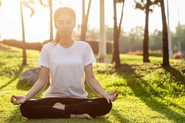 Mulher asiática fazendo exercícios de ioga no parque