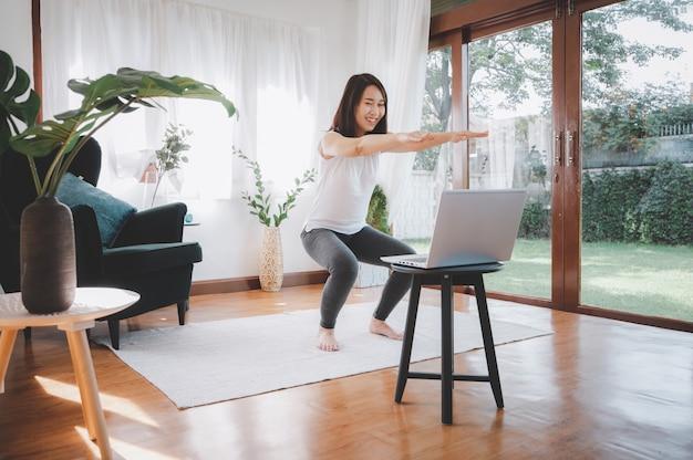 Mulher asiática fazendo exercícios em casa usando um laptop