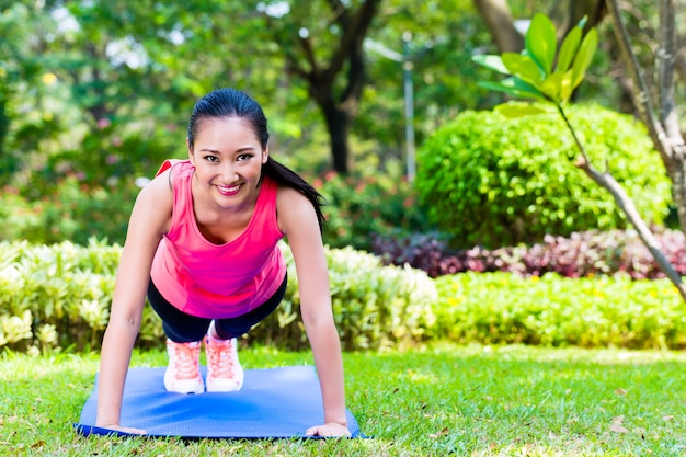 Mulher asiática fazendo flexões no parque