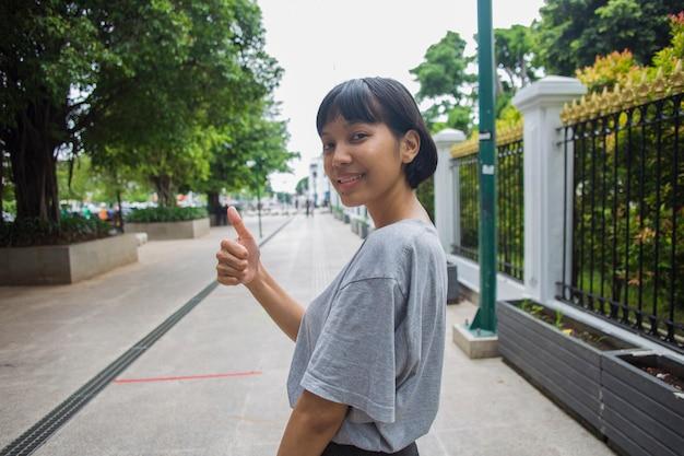 Mulher asiática fazendo gesto de polegar para cima em espaços públicos