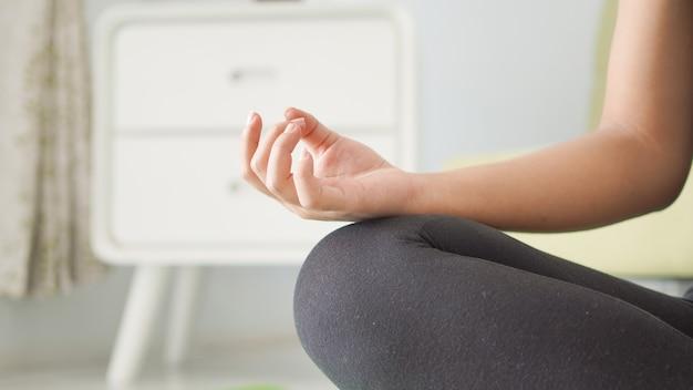 Mulher asiática fazendo ioga com as mãos em casa