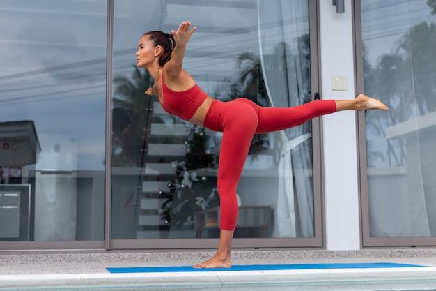 Mulher asiática fazendo ioga do lado de fora da vila perto da piscina mulher com roupa esportiva vermelha faz poses de ioga no tapete