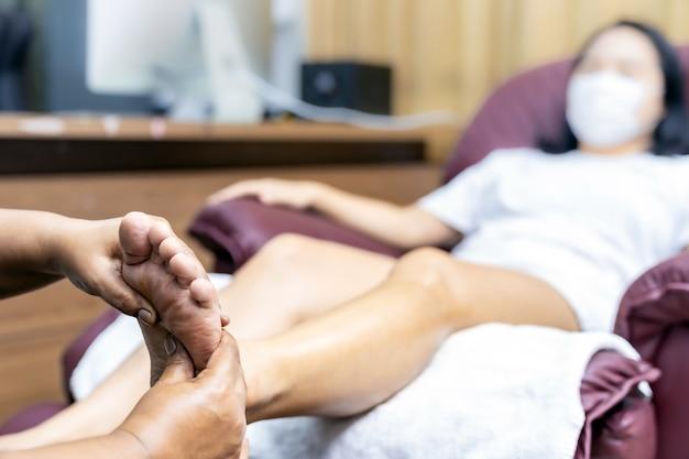 Mulher asiática fazendo massagem nos pés em casa com máscara facial