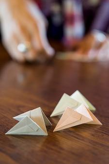 Mulher asiática fazendo origami com papel japonês