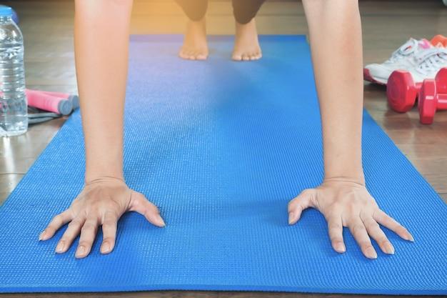 Mulher asiática fazendo pose de prancha completa, conceito de estilo de vida saudável com ioga, vista frontal com luz solar