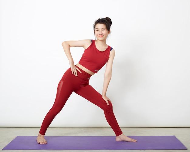 Mulher asiática fazendo pose no tapete de ioga, se exercitando no estúdio