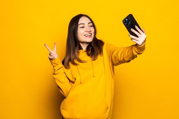 Mulher asiática fazendo selfie foto, videochamada no smartphone na parede amarela com espaço de cópia