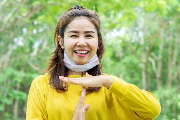 Mulher asiática fazendo um gesto de intervalo durante a crise de saúde de covid -19