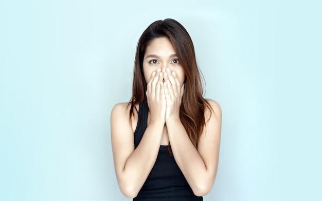 Mulher asiática fechando a mão no nariz enquanto olha para o fundo isolado
