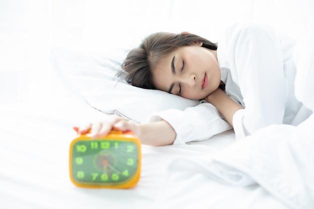 Mulher asiática feliz acordar e desligar o despertador tendo um bom dia