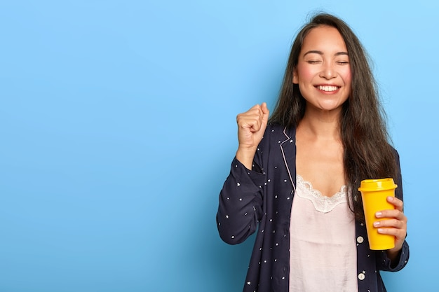 Mulher asiática feliz alegre com longos cabelos escuros, aprecia o café da manhã, fecha os punhos, vestida de pijama, sorri amplamente