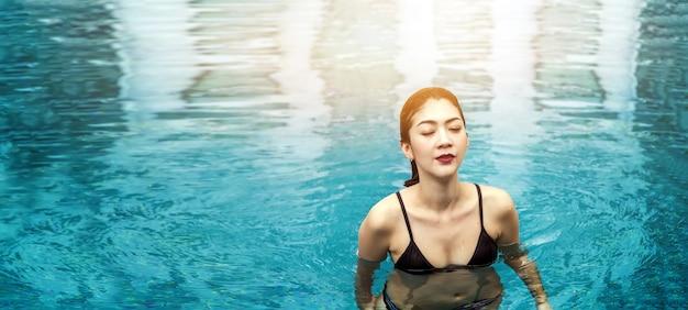 Mulher asiática feliz andando na piscina no verão