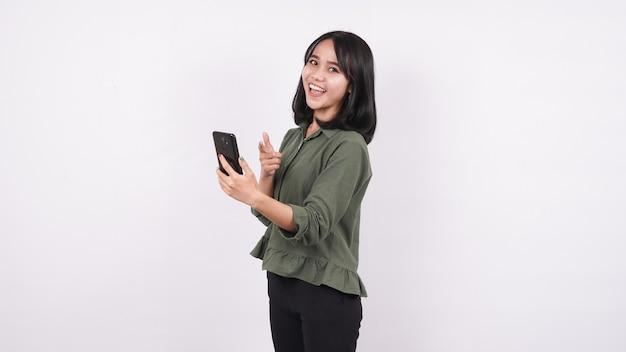 Mulher asiática feliz apontando o telefone em uma parede branca e isolada