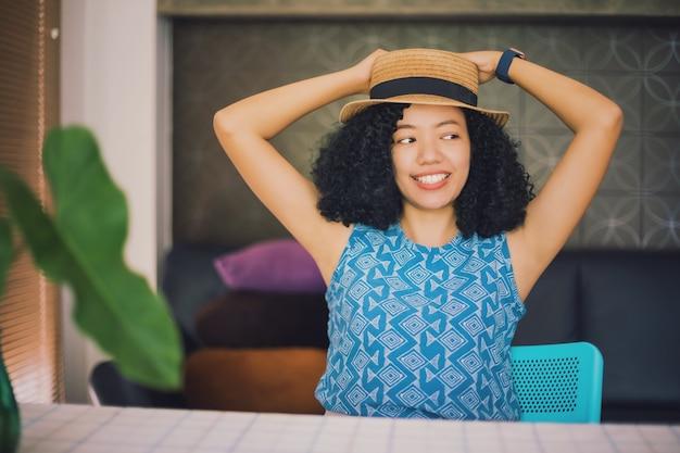 Mulher asiática feliz com cabelo encaracolado preto usando um chapéu, sentada pensando em casa
