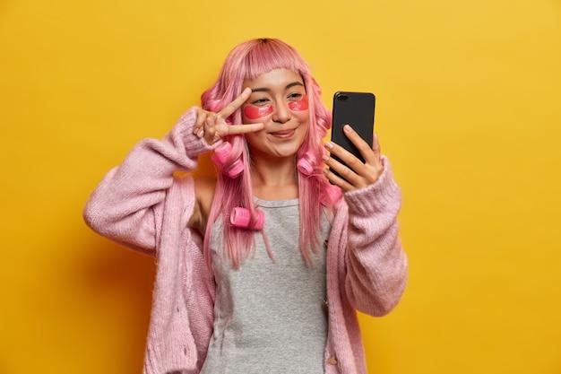 Mulher asiática feliz com cabelo rosa, faz gesto de paz sobre os olhos, tira selfie, aplica adesivos de colágeno sob os olhos
