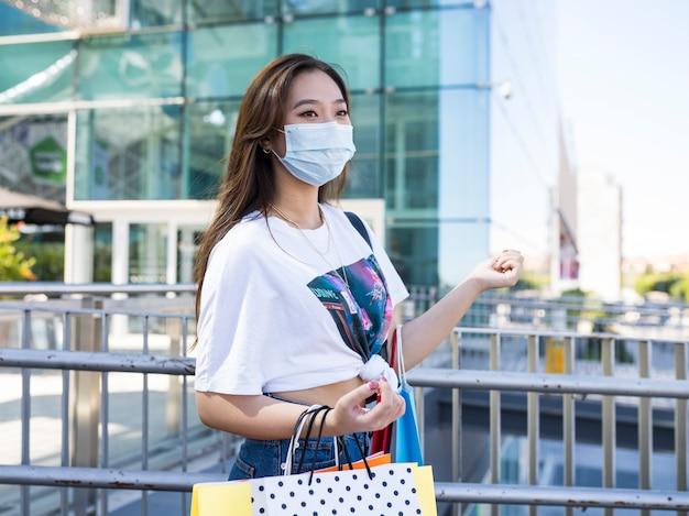 Mulher asiática feliz com máscara de compras