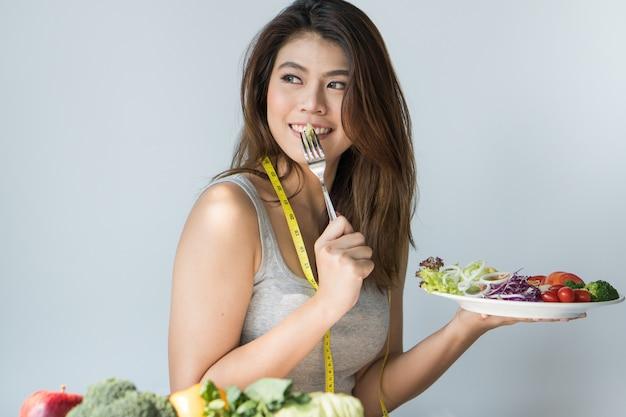 Mulher asiática feliz comendo salada orgânica.