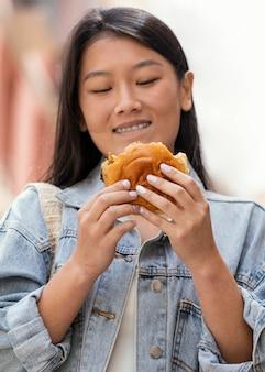 Mulher asiática feliz depois de comprar comida de rua
